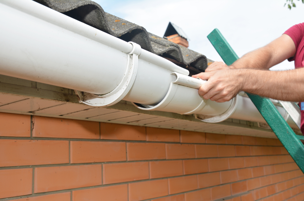A roofers hands and arms can be seen installing a set of white gutters on a brick house.