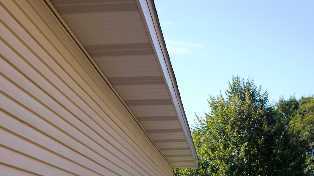 A close up image of aluminum siding and fascia on a yellow house.