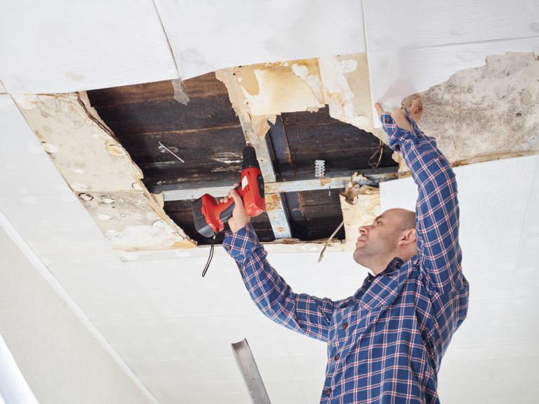 A man in a blue flannel shirt reaches up to repair damaged parts of a ceiling. You can see yellow rot and soft areas, both signs of water damage