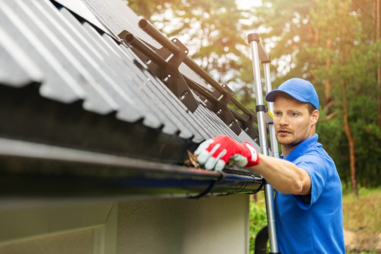 A worker in a blue hat and shirt runs his hand through a set of black gutters on a black roof. He is practicing gutter maintenance.